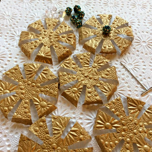 folded embossed gold paper discs with T-pin and beads on embossed paper background