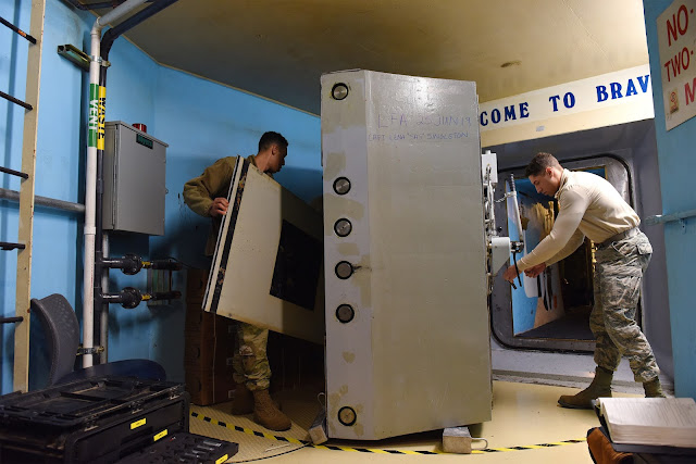 Image Attribute: Airmen service a reinforced door at a U.S. missile alert facility. The facilities would be upgraded or replaced as part of the Ground-Based Strategic Deterrent program. / Source: U.S. Air Force