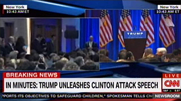 screen cap of CNN coverage showing an empty podium with an all-caps chyron reading: 'IN MINUTES: TRUMP UNLEASHES CLINTON ATTACK SPEECH'