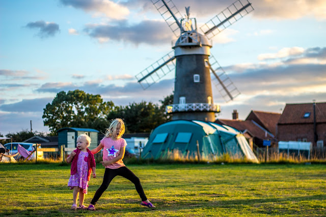 2 children playing with a windmill and tents in the background