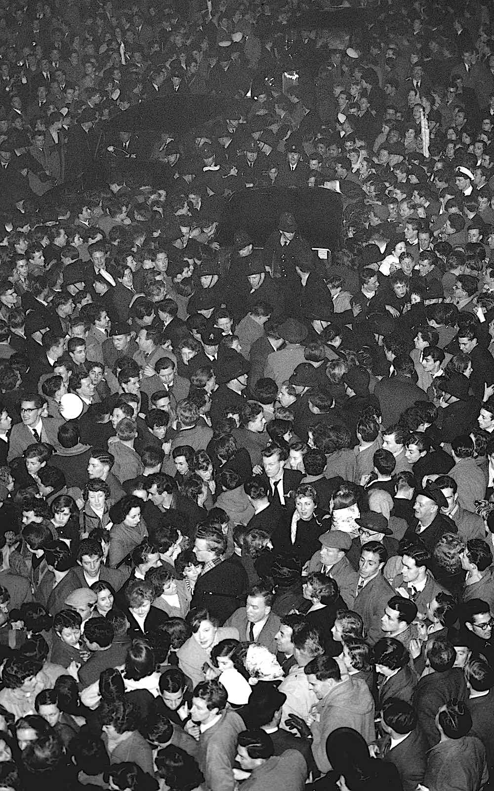 looking down on a crowd of people at night, 1960s?