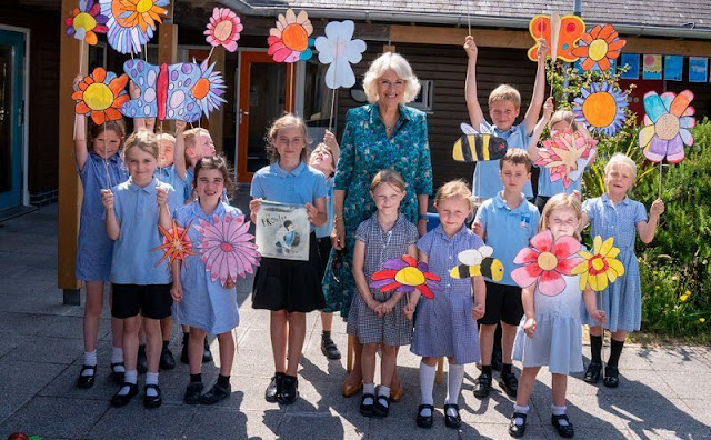 The Duchess wore a hawaiian summery print turquoise blue shirt dress. Prince Charles and Camilla met schoolchildren in St Mary