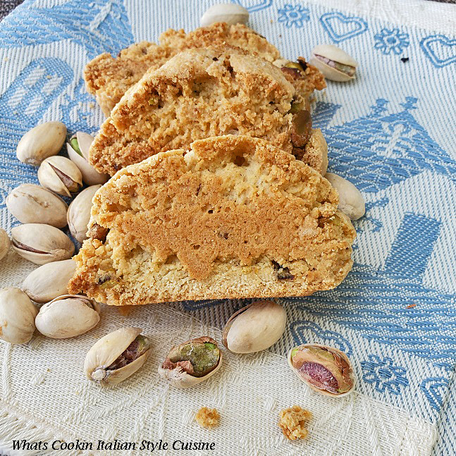 Pistachio Almond Biscotti  on a blue dish towel that came from Rome Italy is in the photo along with shelled roasted pistachio nuts. These are cookies that are a gourmet style in Italy called pistachio biscotti