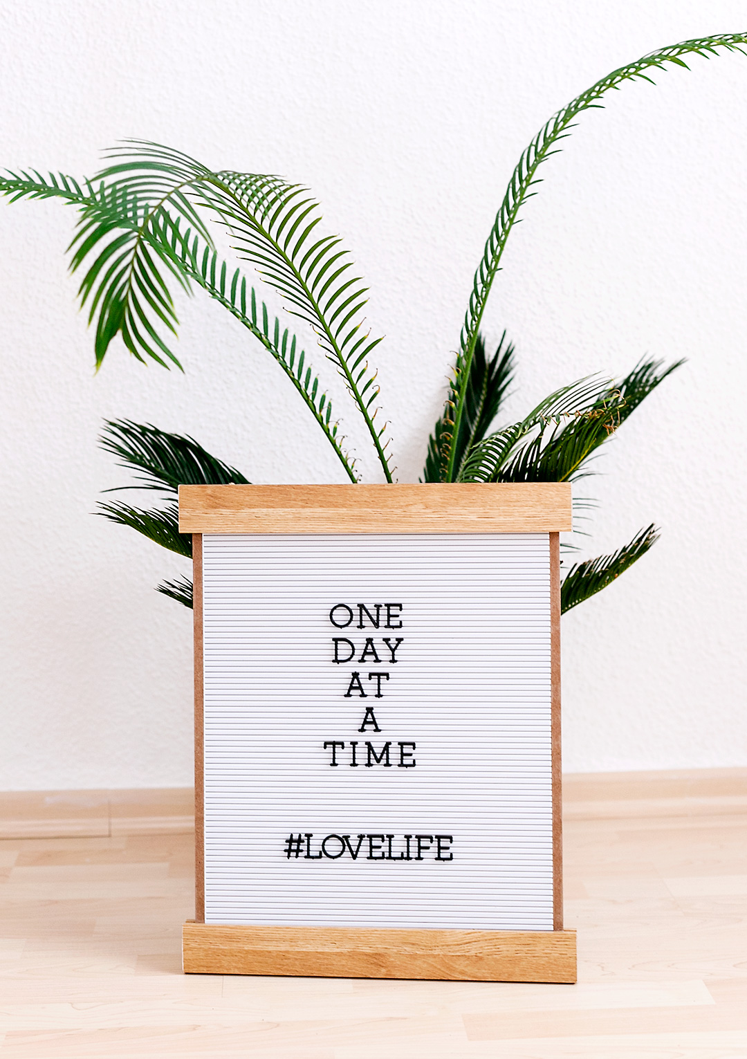 One day at a time quote on a wooden letterboard
