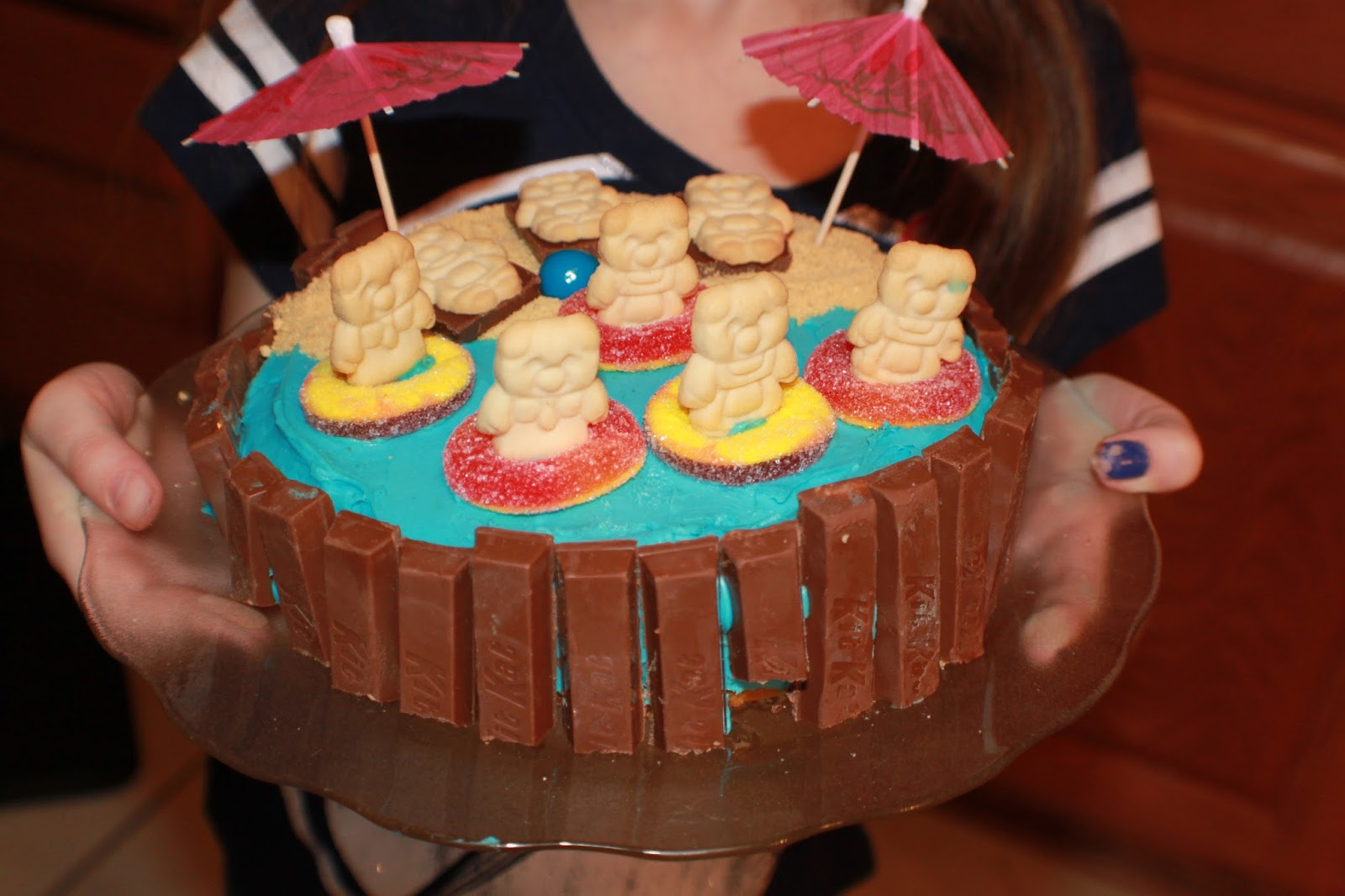 this chocolate cake is frosting, chocolate candy, cookie bears, gummy rings, umbrellas and blue frosting for the water