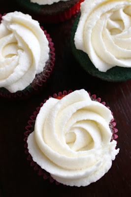 rosettes of cream cheese frosting piped onto cupcakes