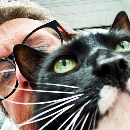 black-and-white cat in the foreground of a man's selfie