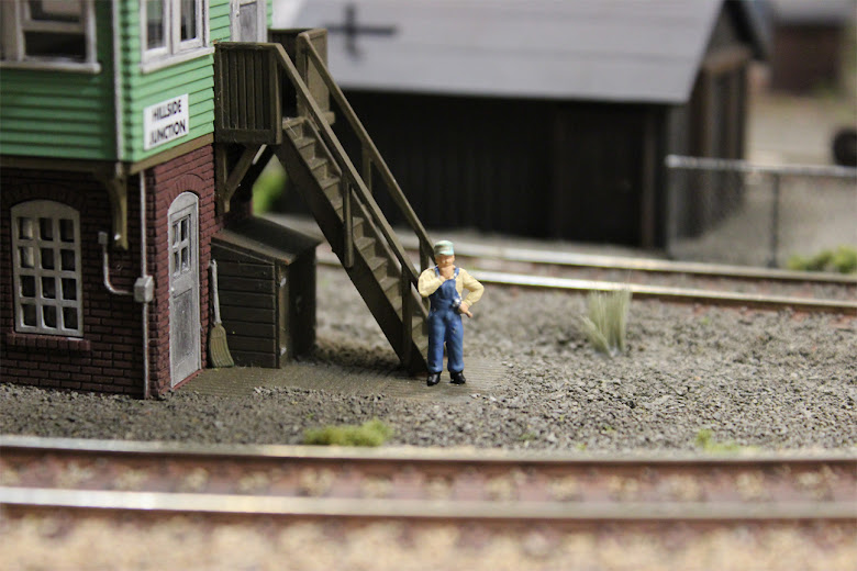 Model train mechanic figure standing in front of the stairs of an Atlas signal tower