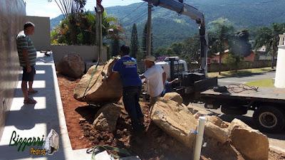 Bizzarri fazendo a execução do paisagismo com pedras com a máquina munck fazendo a colocação das pedras para fazer os canteiros sendo pedras ornamentais do tipo pedra moledo. 7 de março de 2017.