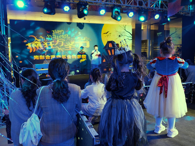 people watching a boy sing a song on a Halloween-themed stage