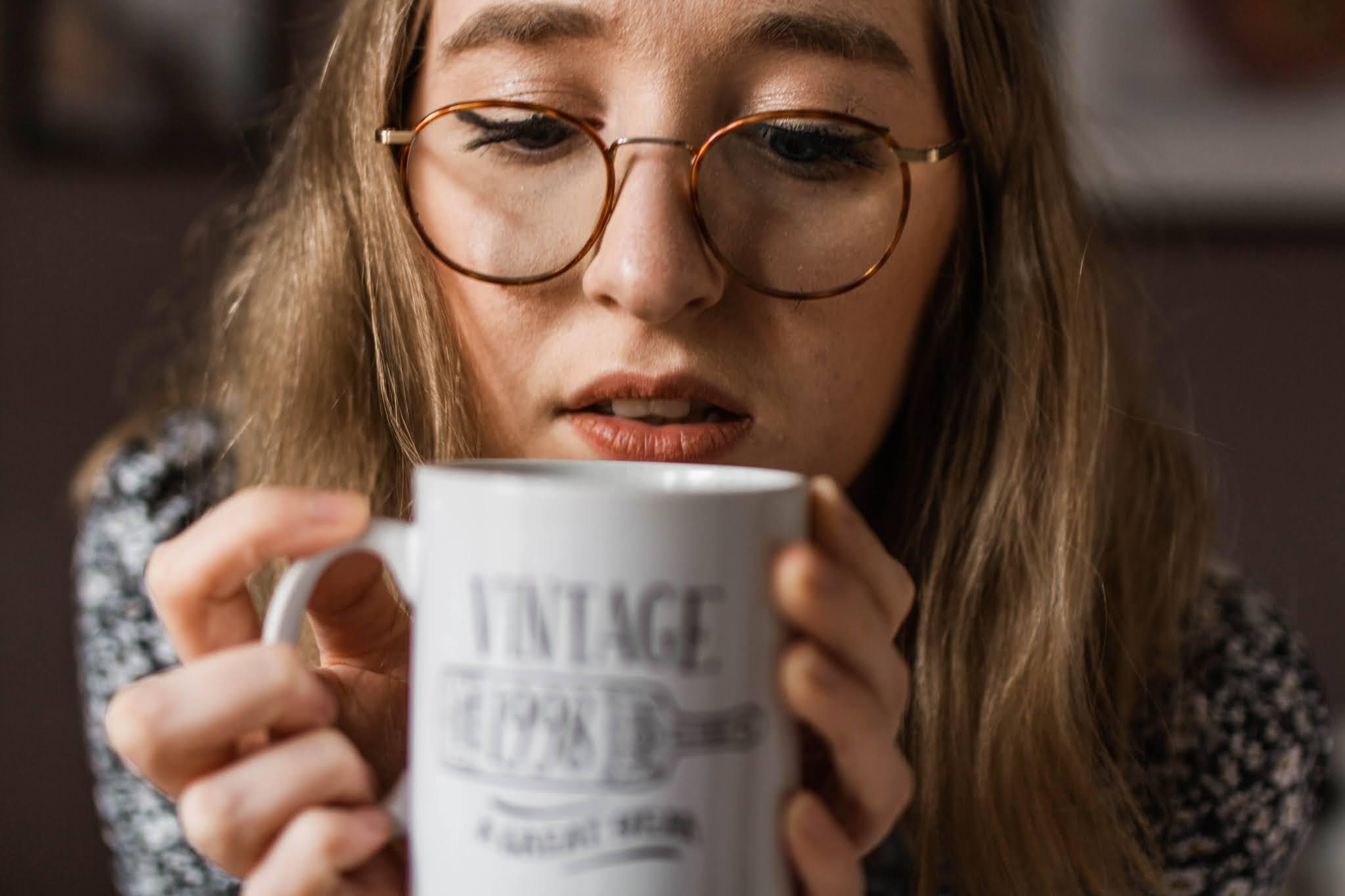 blonde girl with glasses holding white mug