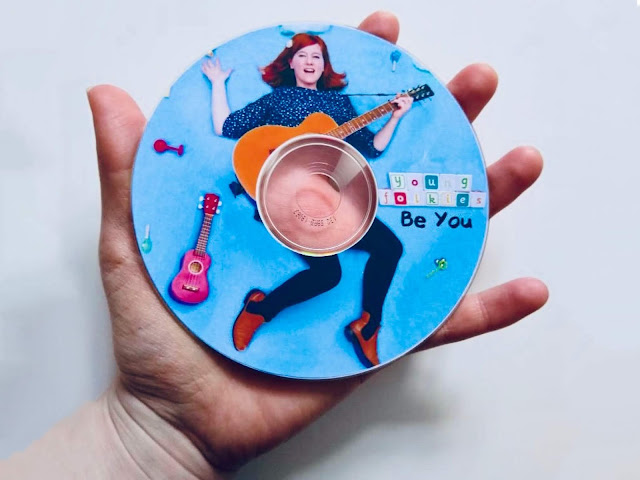 Young Folkies Be You Album on CD being held in a hand