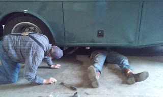 mechanic under an RV while a man watches