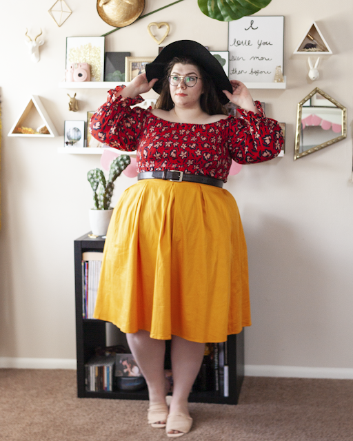 An outfit consisting of a black wide brim floppy hat, a cream and navy blue floral print on red off the shoulder dress with ruffle sleeve hem under a yellow midi skirt and pink slide sandals.