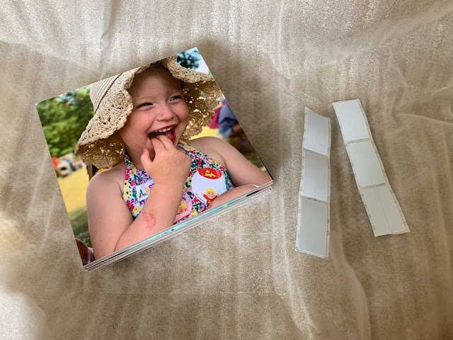 A smiling girl in a photo tile on packaging next to adhesive strips