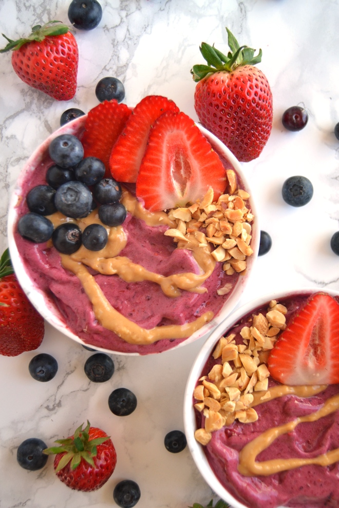 Peanut Butter and Jelly Smoothie Bowls features a thick blueberry smoothie topped with drizzled peanut butter, fruit and crunchy peanuts for the perfect breakfast or snack. www.nutritionistreviews.com