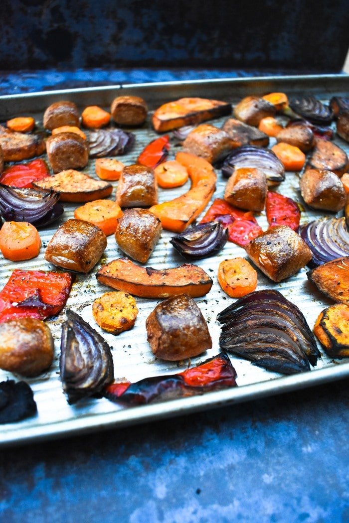 roasted vegetables and sausages on a tray