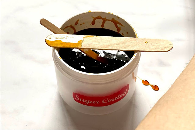 An open post of Sugar Coated home sugar wax with an applicator on top