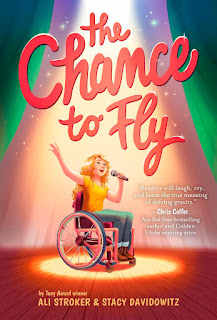 Book cover with the drawing of white girl in a wheelchair. She is holding a microphone and singing with bright spotlight from above.