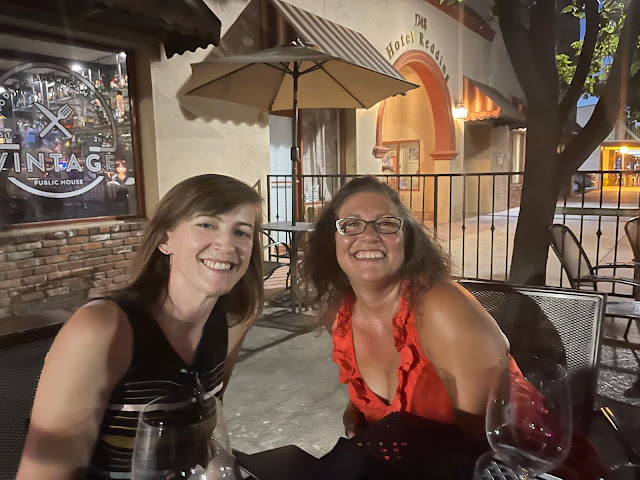 two women sitting outside at a restaurant
