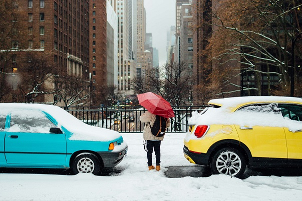 Girl with red umbrella between cars in snowy New York