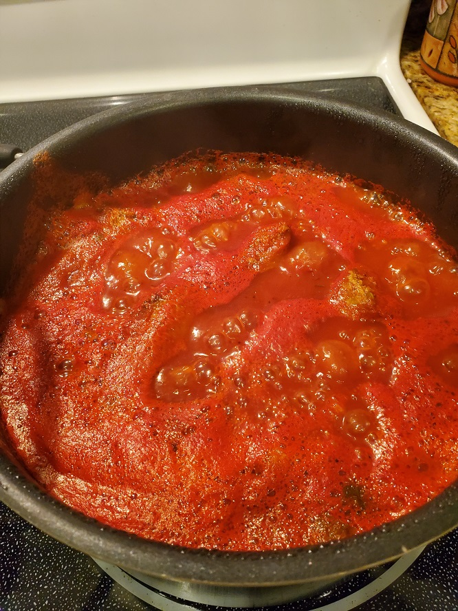 homemade Italian sauce and meatballs in a big pan of tomatoes