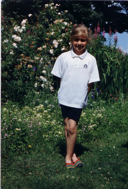 Me as a 10 year old child wearing white tshirt, black shorts and multicoloured shoes in front of flowers