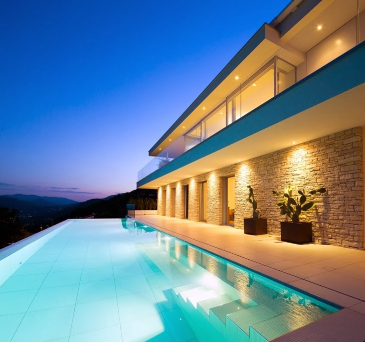 Swimming pool in Beautiful House Lombardo by Philipp Architekten at dusk