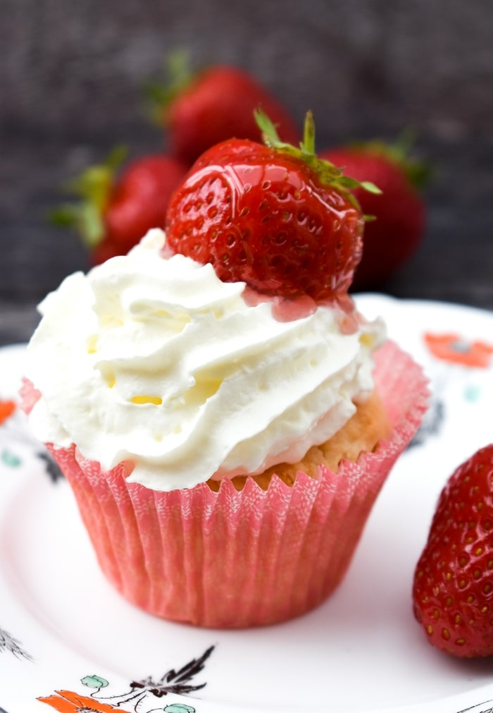 close up of a vanilla muffin topped with whipped cream and a glazed strawberry