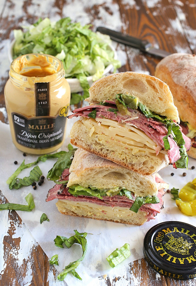 Recipe for an over-stuffed sandwich filled with pastrami, Swiss cheese, shredded lettuce, diced pickles, mayo and mustard on toasted Ciabatta rolls.