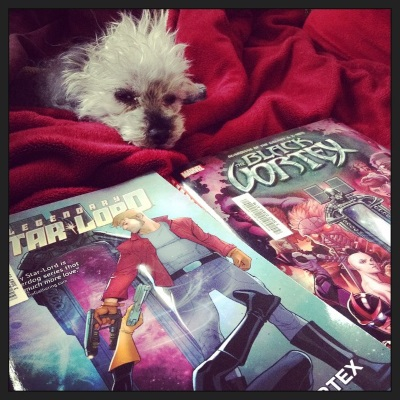 A fuzzy grey poodle, Murchie, lays within a red blanket cave so only his head his visible. His eyes are almost slits, and one of his ears is askew. Two comics lay in front of him. On the one closest to the viewer, a white man in a red jacket points a gun at someone laying on the ground, who points one back at him. On the other, a jumble of people mill around a stand mirror with an elaborate, humanoid frame.