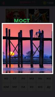 по деревянному мосту вечером едет велосипед с человеком