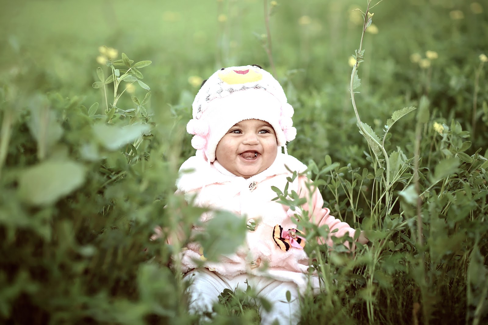 toddler-wearing-white-cap-on-green-field-images