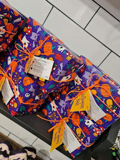 A square box with purple wrapping that also contains orange jack-o-lanterns, black bats and other things on it on a diagonal due to the photo shot on a large light brown rectangular shelf on a bright background