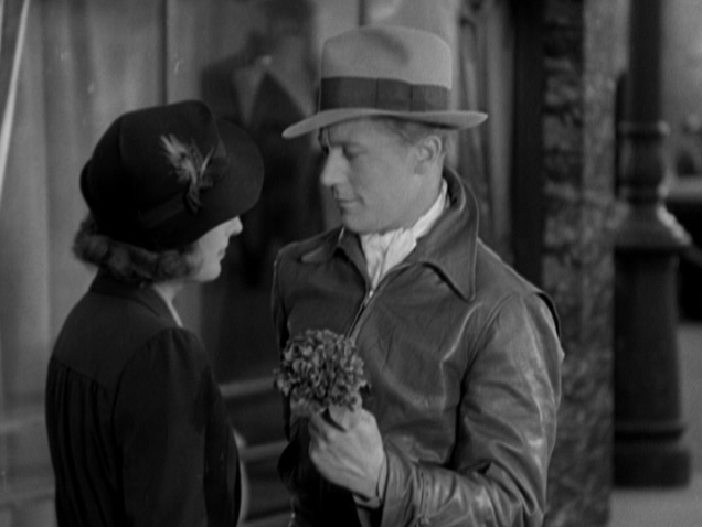 Michael (Gene Raymond) offers Carolyn (Barbara Stanwyck) a small modest bouquet of flowers.