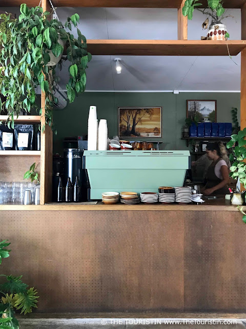 A green coffee machine and brown and yellow coloured plates stacked on a rustic cafe counter. Decorated with green plants.