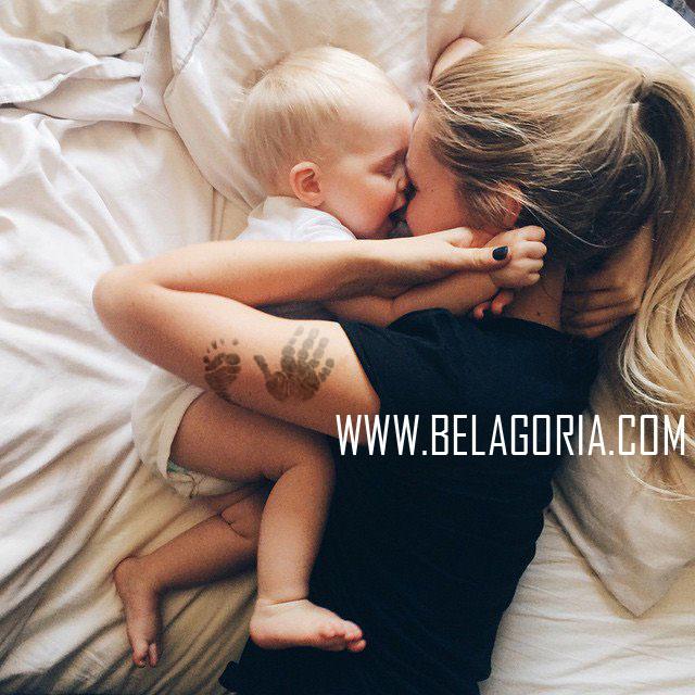 preciosa fotografia de una madre y su bebe jugando, la madre lleva tatuaje de las huellas del bebe en el brazo