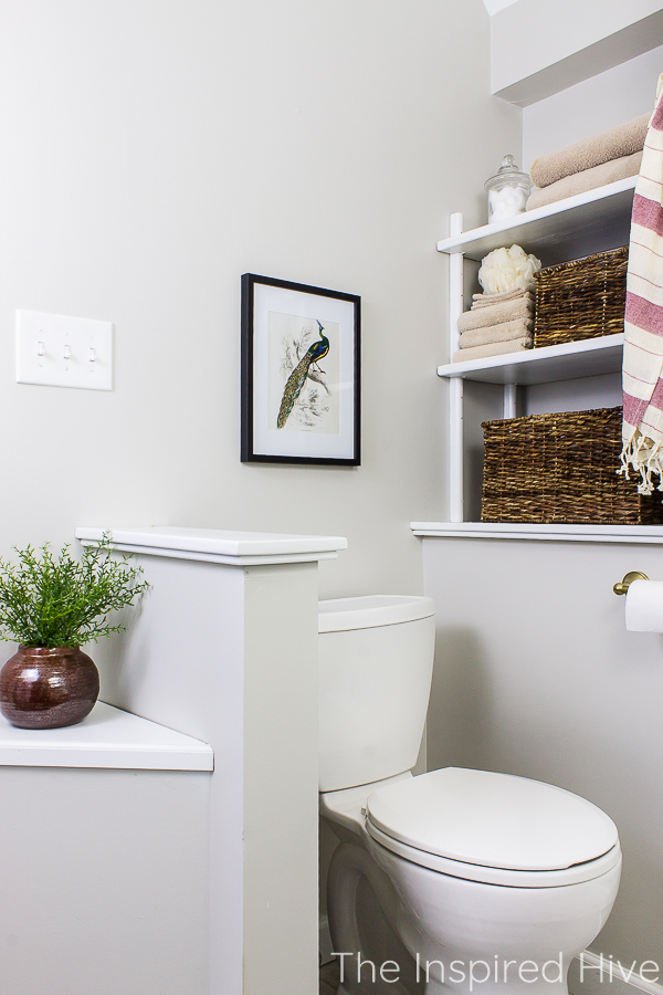 Toilet nook with half wall. Peacock art in black frame, baskets on open shelves.