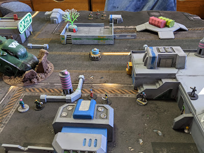 Tabletop view of minis and terrain for a sci-fi game.