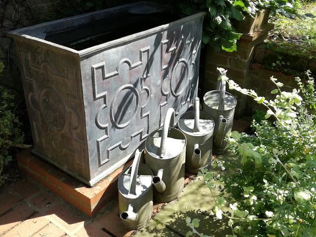 ołowiana donica i konewki , ozdoby ogrodowe