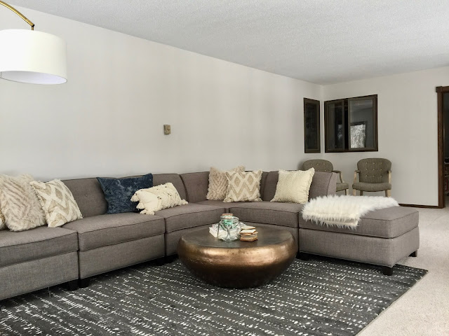 neutral grey, cream, and black living room with grey sectional sofa and arched lamp,