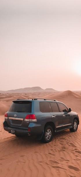خلفية سيارة الدفع الرباعي تويوتا فوق رمال الصحراء البنية