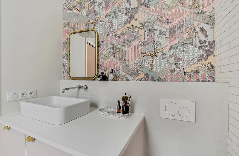 Baño con mobiliario rosa, encimera de mármol y espejo vintage. Papel pintado femenino.