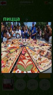 сделана огромная пицца, которая стоит на улице и вокруг люди