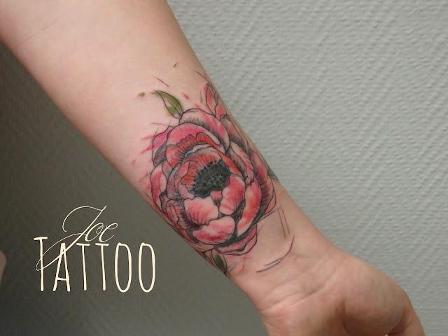 pour représenter sa maman décédée, Manon a recouvert un ancien tatouage avec une fleur de pivoine dans le style trash graphique, avec des éclats de couleur en rose et vert pour le feuillage