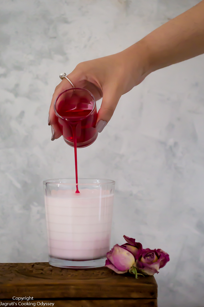 pouring shot of rose lassi with rose syrup