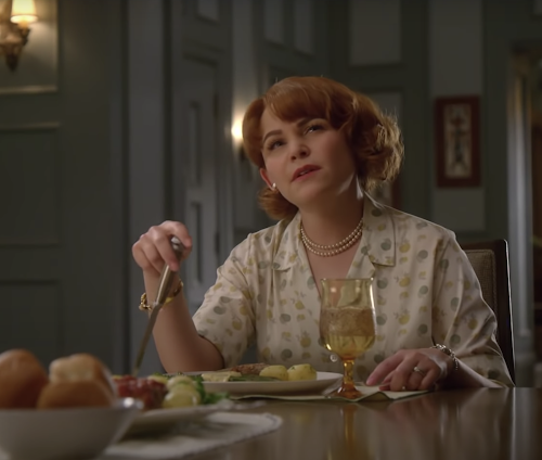 Ginnifer Goodwin in Why Women Kill. Ginnifer is sitting at the dinner table and has a thoughtful expression on her face.