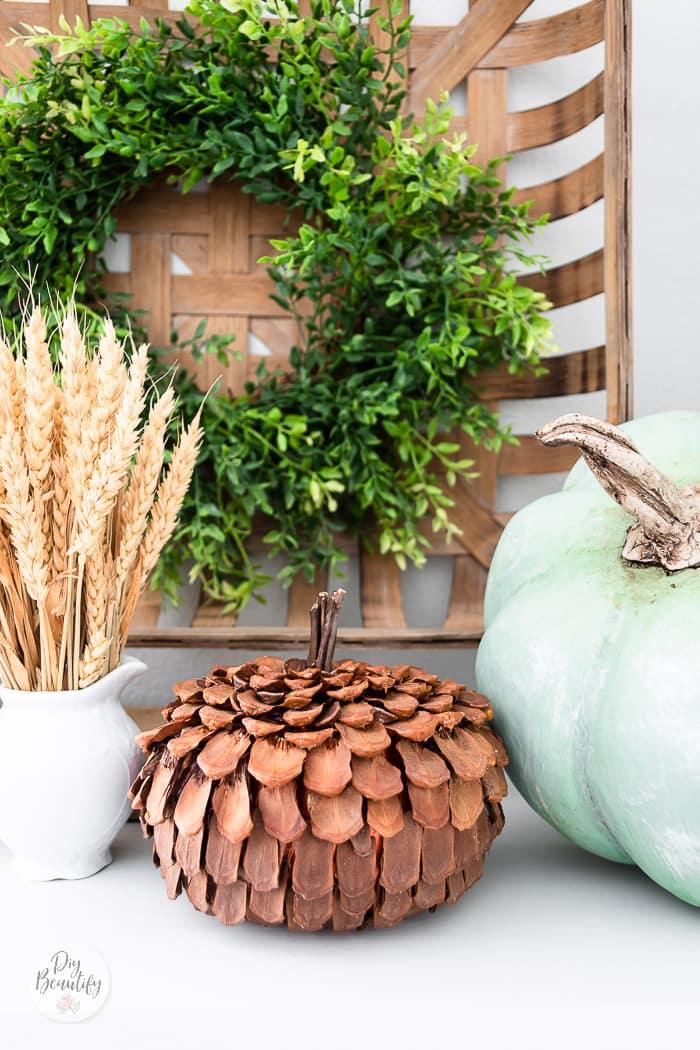 pinecone pumpkin on display with heirloom Cinderella green pumpkin, tobacco basket and greenery wreath