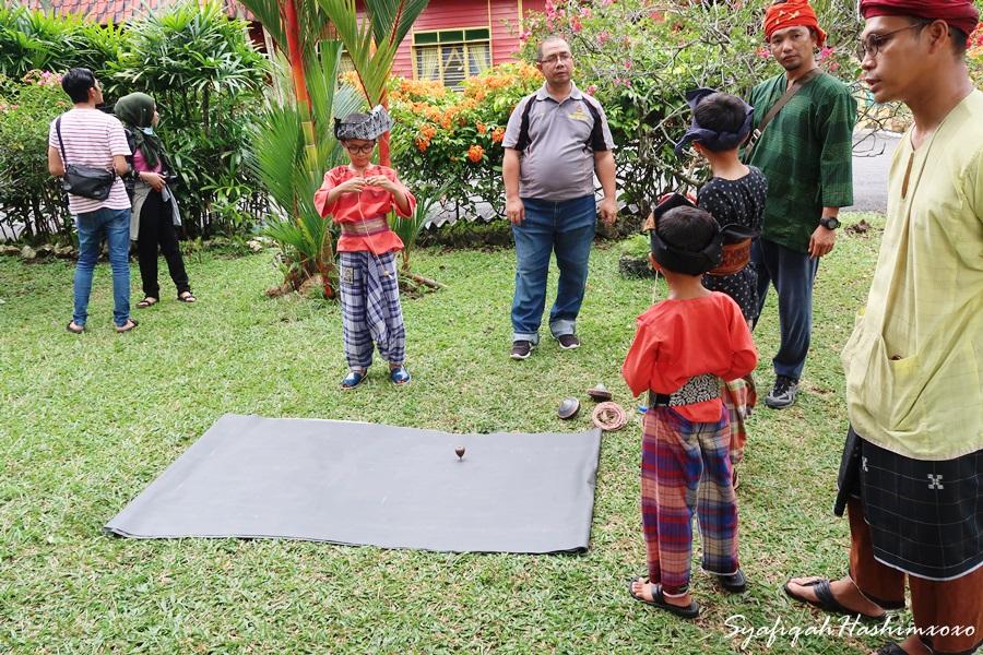 kanak-kanak sedang demonstrasi permainan Gasing