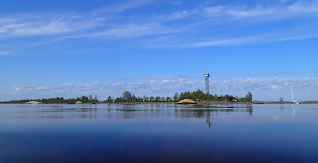Puustoinen saari ja vartiotorni tyynen veden yli katsottuna